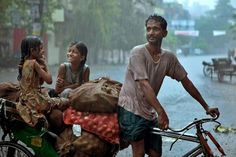 Two girls laugh as a soaked rickshaw driver transports vegetables during a monsoon.