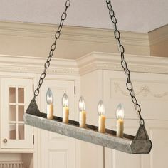 okay- I wouldn't use this as a chandelier, those fake candles are not my style, but I never thought about setting a galvanized trough out on a coffee table or sofa table with real candles in instead, or even filling with moss and plants.