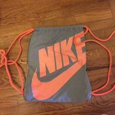 Nike drawstring back w/ side pocket This is a gray Nike drawstring bag with orange Nike lettering. It has a side zipper pocket on the outside, and a pocket on the inside. It has been used, but is in great condition. Nike Bags