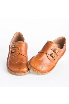 Perfect for wearing back to school and all winter long, these camel brown leather shoes are decorated with two brass buckles and swirling dot cutouts on the toe. With a hidden elastic panel on the inside of the instep for a little extra stretch, and durable rubber soles. By Pepe.