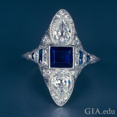 An emerald-cut sapphire sitting between two pear-shaped diamonds