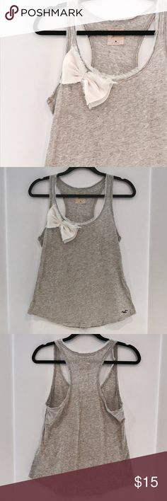 Grey Racer Back Tank Top with Bow Light Grey Racer Back Tank Top with cute layered bow and fringed sleeves. Material: 100% cotton. CONDITION: Used, Great Condition Hollister Tops Tank Tops