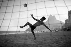 Everyday, football is played out in all corners of Rio and on its beaches, as people show off their skills. Here, a player acrobatically performs a bicyclette on Leblon beach beneath the backdrop of Rio's famous two brothers mountains (Dois Irmãos). Picture: Tony Burns