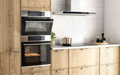 Stekeovn og ventilator i rustfritt stål på et kjøkken i eik med benkeplater og håndtak i aluminium.