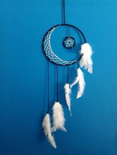 Traumfänger aus dunkelblauem Garn, weißem Faden und weißen Vogelfedern