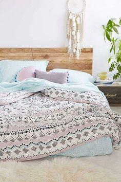 Des couleurs pastel sur le linge de lit et un cadre en bois, cette chambre a tout d'une pièce cocooning. Le tapis fourrure au sol renforce l'effet confort nid douillet.