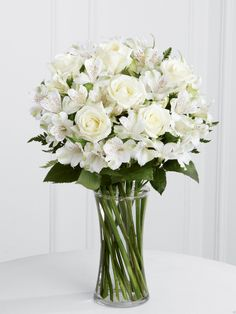 Vased white alstroemeria and standard roses.  Alstroemeria Bridal bouquet.  Purvian Lilies are available in pinks, lavender, purple, yellow, peach, white and deep purple (as well as variegated colors).  They are a long lasting flowers that is great for bouquets, centerpieces, corsages and boutonnieres.