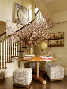 Fill an empty corner with a round table and stools. If you are lucky enough to have a bit of space in your entryway. A round table softens up a blank corner and provides the perfect spot for a few extra seats.