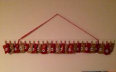 Adventskalender. En bit golvlist, små klädnypor, washitape. Påsar gjorda av julklappspapper. gjord av mig efter div inspiration