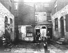 A narrow court of the 1930's, as pictured, was typical of working class housing in the Scotland Road area of Liverpool in the early 1900's. Such a court would usually contain six houses with a frontage of only ten feet. In such cramped accommodation there were frequently as many as sixty people in a single court all using the one tap. In an effort to make the dark miserable courts brighter the residents 'whitewashed' the walls. Yet despite having to tolerate such poor living conditions…