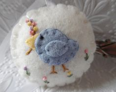 Felt Bird Pincushion Fob Scissor Charm Penny Rug Applique  Hello, welcome and thanks for stopping by.  This little bird pincushion/FOB charm is made from top quality felted wool in a med. rose color and bright white. Tiny bird was hand appliqued and the flowers were made from pastel blue and bright pink DMC embroidery thread, the branch in the birds beak and tiny feet are also hand embroided.  Center is filled with poly fill and the ribbon is sewn into the center. The FOB was wrapped on ...