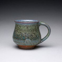 This wheel thrown stoneware mug is glazed with a combination of a green wood ash glaze and an orange shino. The pattern of spots on the green