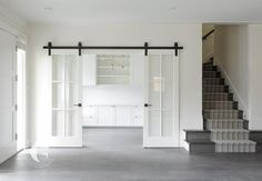 Sliding glass paneled white doors on bronze rails slide open to reveal a white h. Sliding glass paneled white doors on bronze rails slide open to reveal a white home office fitted w Interior Flat, Interior Barn Doors, Interior Design, Sliding Door Design, Sliding Glass Barn Doors, Barn Door With Glass, Kitchen Sliding Doors, Sliding French Doors, The Doors
