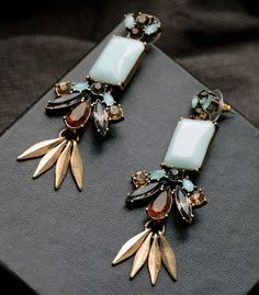 A stunning mix of hand-set black, aqua and neutral stones combine to make a radiant and elegant chandelier earring. Materials::Alloy,Resin, Glass Size::7.8*3cm The weight::37g