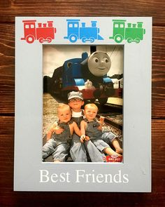 This listing is for a hand-painted personalized 5x7 glassless photo frame. This design is Thomas the Train-inspired! The wooden frame features a backing to hold your photo in place and has four keyhole mounts: two for vertical and two for horizontal hanging. The frame is 11.5 x 9.5 and 1/2 thick. Some frames are 9 3/4 x 7 3/4 and 3/4 thick with two dowel holes and one dowel and a moveable hanger for easy hanging, either vertically or horizontally. Both frames hold a 5x7 ph...