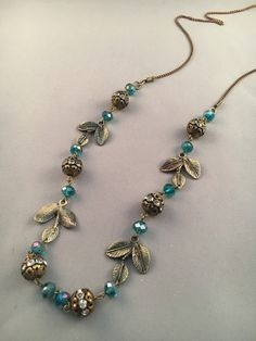 This necklace will get you lots of comments when they see the aqua colored faceted beads and antique gold balls with leaves. The antique gold chain completes the picture.