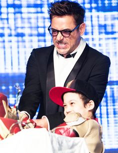 "Robert Downey Jr. cuts his birthday cake -- with the help of a young fan -- in Seoul, South Korea during the international ""Iron Man 3"" press tour (April 4, 2013)."