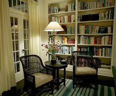 my ideal living room-- Huge bookshelf, cozy chairs, soft but bright lamp, and french doors and trestle windows!