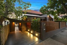 House exterior with dark paint exterior and concrete driveway and outdoor lighting