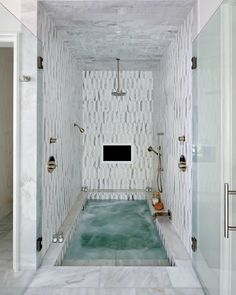 Stunning spa shower boasts white and gray marble tiles and ceiling fitted with a built in TV and a circular rain shower head and sprayer aimed over a sunken bathtub with steps leading out through double glass doors to white marble floors. Source by Dream Bathrooms, Beautiful Bathrooms, Small Bathroom, Master Bathroom, Bathroom Spa, Bathroom Ideas, Bathtub Ideas, Master Baths, Master Shower