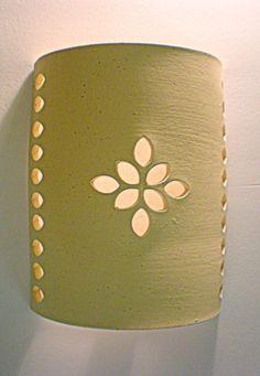 מנורת קיר מקרמיקה בעבודת יד, בגוון שמנת, בגימור גלזורה מט. במידות רוחב 14 ס''מ, גובה 16 ס''מ, עומק 8 ס''מ. האור מתפזר כלפי מעלה ומטה וכן דרך העלים שבדוגמת התחרה. ניתן להזמין את המנורה במידות שונות וכן בצבעי חימר שונים. ניתן גם להזמין את המנורה עם גלזורה שקופה או צבעונית. (הזמנות מיוחדות יחויבו במחיר המלא של המוצר). Slab Pottery, Ceramic Pottery, Ceramic Art, Diwali Decorations, Light Decorations, Ceramic Light, Pottery Classes, Lamp Bases, Light Shades