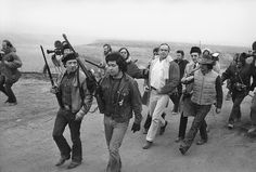 Description of  Harlington Wood, Assistant U.S. Attorney General, (white shirt) is escorted by armed members of AIM into the village of Wounded Knee, South Dakota, March 13, 1973 to meet with leaders. Wood was sent to the village held for the last two weeks by the militants in an effort to work out a solution to the problem. (AP Photo)