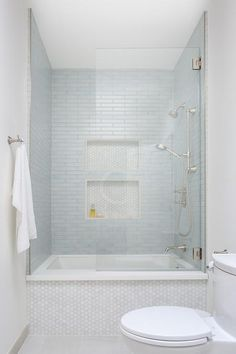 Thin blue staggered bath shower tiles in a white marble hex tiled bathtub enclosed with a glass partition. Thin blue staggered bath shower tiles in a white marble hex tiled bathtub enclosed with a glass partition. Glass Tile Shower, Bathtub Shower Combo, Bathroom Tub Shower, Tub And Shower, Bathtub With Glass Door, White Tile Shower, Shower Over Bath, Bathtub Remodel, Shower Remodel