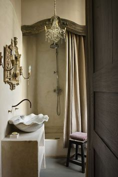 Gorgeous French bathroom design with scalloped stone vessel sink, wall-mount faucet, gilt mirror flanked by French sconces, arched shower nook, rain shower head, stucco walls and crystal chandelier.