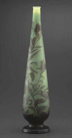 Vase piriforme sur talon signé Gallé en verre multicouche, décor de fleurs et branchages mauves sur fond vert sapin, h. 47,5 cm