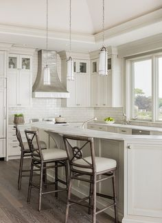 Gorgeous kitchen features a ivory cabinets paired with white marble countertops and a glazed ivory subway tiled backsplash.