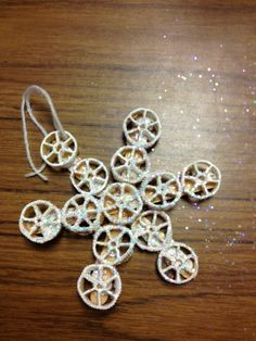 Snowflake ornament made with popsicle sticks and wagonwheel pasta.