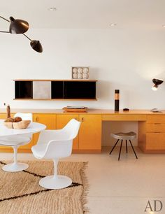 The kitchen features a Saarinen Tulip table and chairs by Knoll and built-in cabinets by Neutra; the hanging cabinet and stool are by Jean Prouvé.