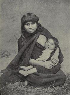 Mujer Mapuche y niño (ca. 1909) / Los mapuches o araucanos (nombre dado por los españoles a los indígenas que habitaban la región histórica de Araucania o Arauco), son un peblo que habita el sur de Chile y Argentina, vía Wikipedia