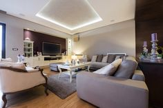 TV and entertainment room with tray ceiling, wood floor and large sectional sofa