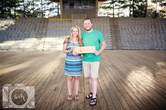 Standing holding wooden sign engagement picture at Worlds Fair Site by Amanda May Photos