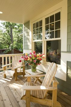 A simple pine front porch with a pair of wooden lounge chairs. The small side table has a glass vase full of gorgeous tulips.