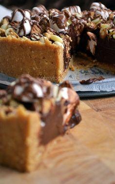 Rocky Road taartWat heb je nodig? (1 taart van ± 20 cm)  Voor de taart:    ◦250 gram volkeren biscuits (bijvoorbeeld Digestives van Verkade)  ◦een klein handje pinda's  ◦5 Jodekoeken  ◦180 gram zachte roomboter  ◦250 gram pure chocolade  ◦250 ml ongeklopte slagroom  ◦2 eidooiers  Decoratie:    ◦marshmallows  ◦gebroken biscuitjes  ◦witte chocolatchips  ◦melkchocolade om te smelten
