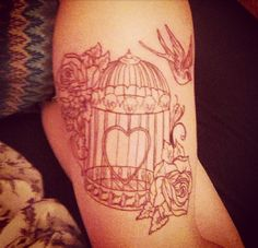 This cage in black with two red roses and birds flying out