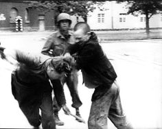 A freed Jewish prisoner expresses his rage and beats down a German guard at the liberated Dachau Concentration Camp. An American soldier looks on and does not interfere. Germany, 1945