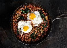 Spinach with Chickpeas and Fried Eggs -- We love the frilly edges of olive oil–fried eggs. Serve them over chickpeas for a vegetarian main.