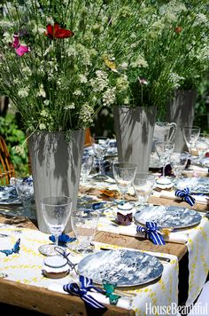 """Textile designer Michael Devine conjures a romantic, swoon-worthy alfresco fete. """"To complement the floral arrangements, I chose crisp yellow-and-white table runners in my Chantal fabric,"""" he says. """"Vintage blue-and-white chinoiserie-pattern dinnerware was paired with napkins tied with striped ribbon."""" He wired fanciful faux butterflies into the arrangements, making them appear to be fluttering throughout the Queen Anne's lace.   - HouseBeautiful.com"""
