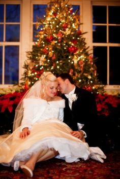 A couple poses for a sweet moment in front of a brightly-lit Christmas tree at the Oakmont Country Club in Pittsburgh. The greens and reds of the tree and the poinsettias surrounding it brightly contrast the pristine white and sharp black of her fur-trimmed jacket and gown and his tuxedo. The couple was married at the Oakmont Country Club in Pittsburgh, where they celebrated with their guests to the festive sounds of The John Parker Band. http://www.jpband.com/weddings.html