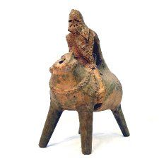 Pottery aquamanile; in form of mounted knight; yellow glaze; head of horse missing; handle from knight's head to horse's tail; legs are modern.