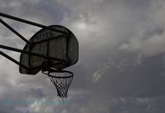 Basketball backboard and int with dark skies in spring.