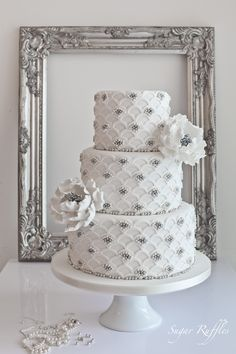 This immaculate white-and-silver wedding cake features scalloped details along with silver and pearl strewn throughout