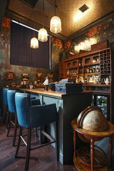 the Lost and Found - Birmingham. Globes, apothecary style back bar, tin ceiling, floral wallpaper & bric a brac