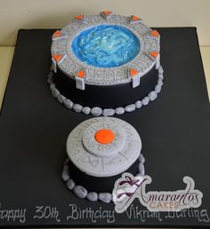 "Stargate cake with corresponding ""Dial Home Device"" (DHD) cupcake.  Mike would appreciate a DHD to complete the set.  :)   I like the distinction in colors from the base of the cake and the Stargate itself.  The rock/pebble items are unnecessary though."