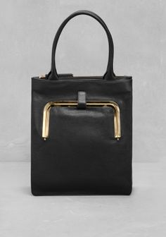 A structured leather tote featuring an outside metal-edge pocket for an easy access to credit cards and everyday essentials.
