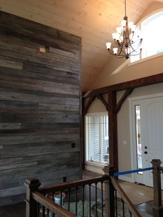 reclaimed barnwood accent wall in entry way of reclaimed barnwood beam timber frame house built by: www.BenedictBarns.com