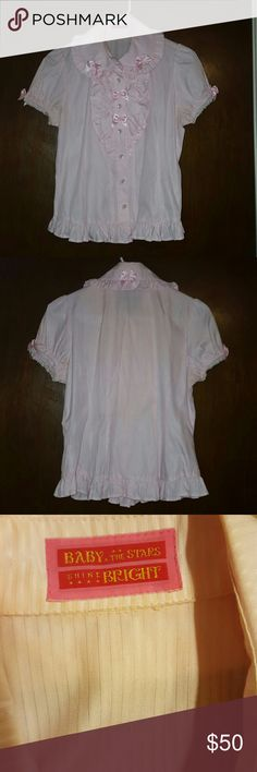 """BTSSB pink blouse Authentic Japanese brand Baby the Stars Shine Bright blouse in pink. Puff sleeves, frills, and shimmery pinstripes. Many small bow accents. Perfect under lolita jsks or over a skirt. Worn a handful of times, but some of the buttons had to be resewn at time of original purchase and are loose again. Spare button intact.  60% cotton, 40% polyester This is a one-size article, but fits about a US size 2-4 Shoulder width: 13.5"""" (34 cm) Length from shoulder to hem: 20"""" (51 cm)…"""